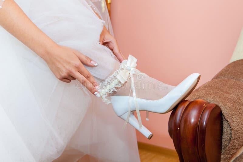 Giarrettiera di nozze sulla gamba del ` s della sposa immagini stock