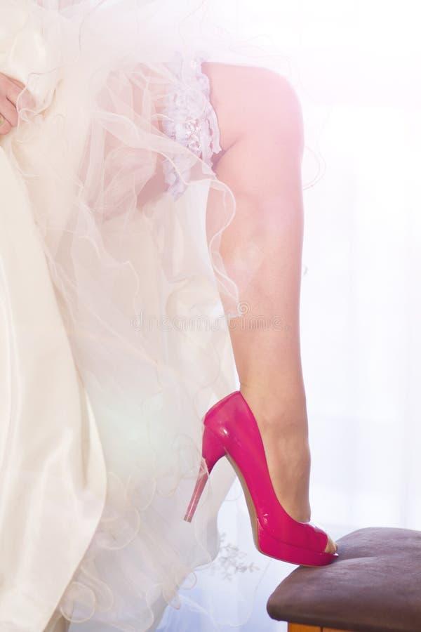 Giarrettiera sulla gamba di una sposa immagine stock