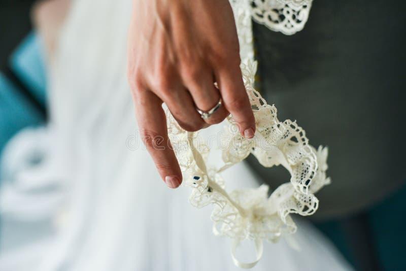 Giarrettiera sulla gamba di una sposa, momenti di giorno delle nozze immagini stock libere da diritti