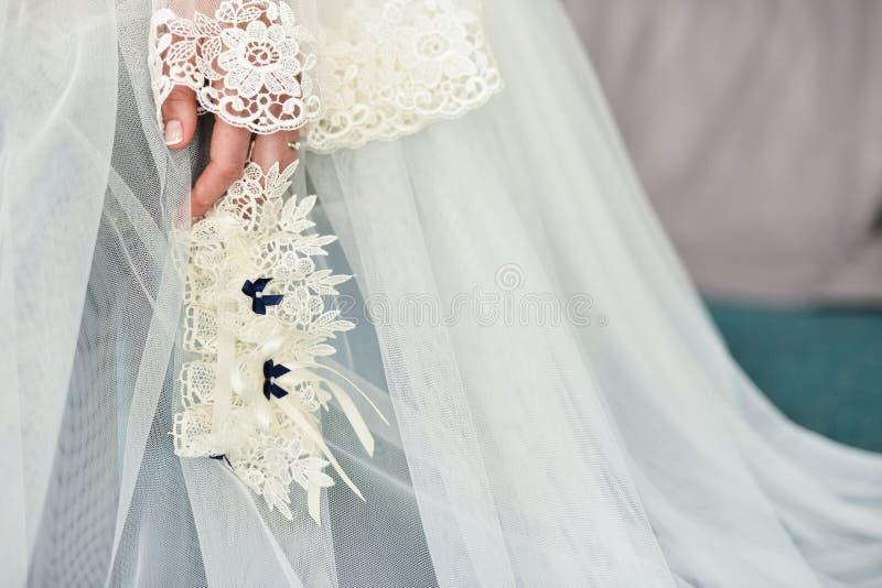 Giarrettiera sulla gamba di una sposa, momenti di giorno delle nozze fotografia stock
