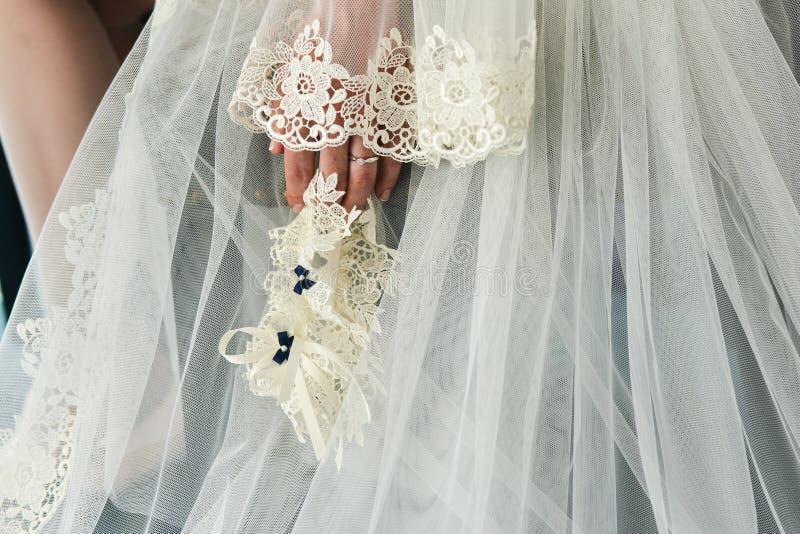 Giarrettiera sulla gamba di una sposa, momenti di giorno delle nozze immagine stock
