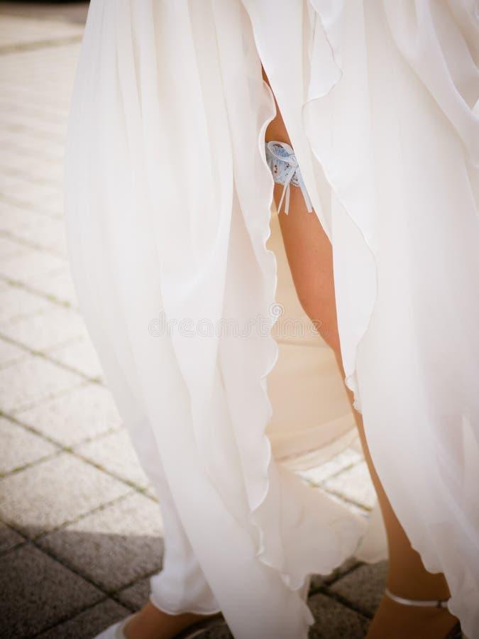 Giarrettiera sulla gamba di una sposa, sposa sexy esile in vestito di lusso da nozze che mostra la sua giarrettiera di seta con i immagine stock