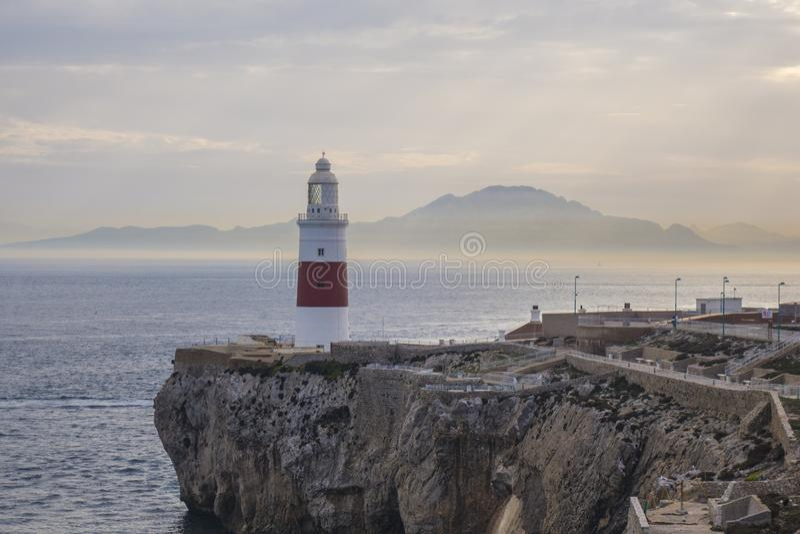 Gibraltar-Leuchtturm auf Klippe durch Meer mit Bergen herein weit lizenzfreies stockbild