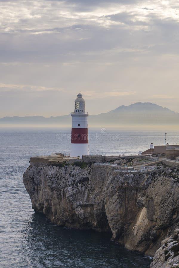 Gibraltar-Leuchtturm auf Klippe durch Meer mit Bergen herein weit lizenzfreie stockbilder