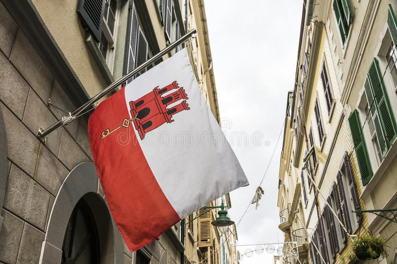 Flag of Gibraltar. Gibraltar, UK. Flag of Gibraltar waving from one of the houses in Main Street. A British overseas territory disputed by Spain stock image