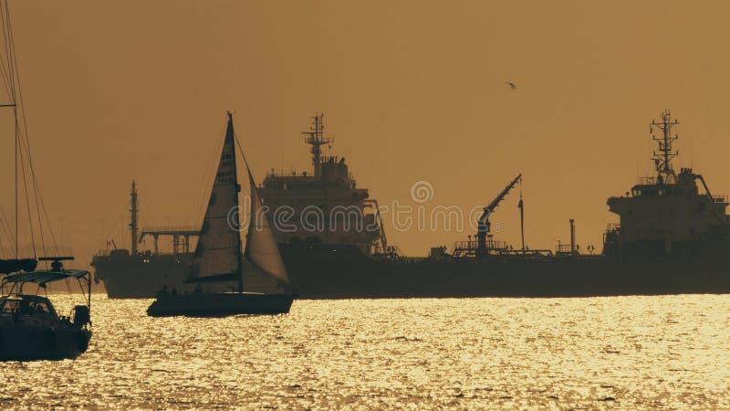 GIBRALTAR WIELKI BRYTANIA, WRZESIEŃ, - 27, 2018 Sylwetka manewrować żaglówkę i odległych ładunków statki przy zmierzchem zdjęcia stock