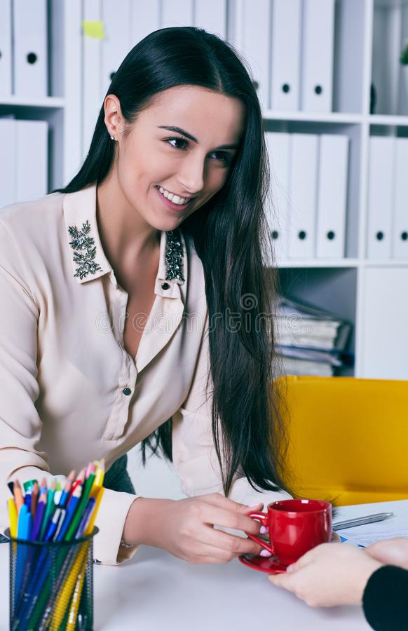 Gibt lächelnder weiblicher Büroangestellter der Junge dem Bürobesucher Tasse Kaffee, der am Tisch sitzt Büroservicekonzept lizenzfreies stockfoto
