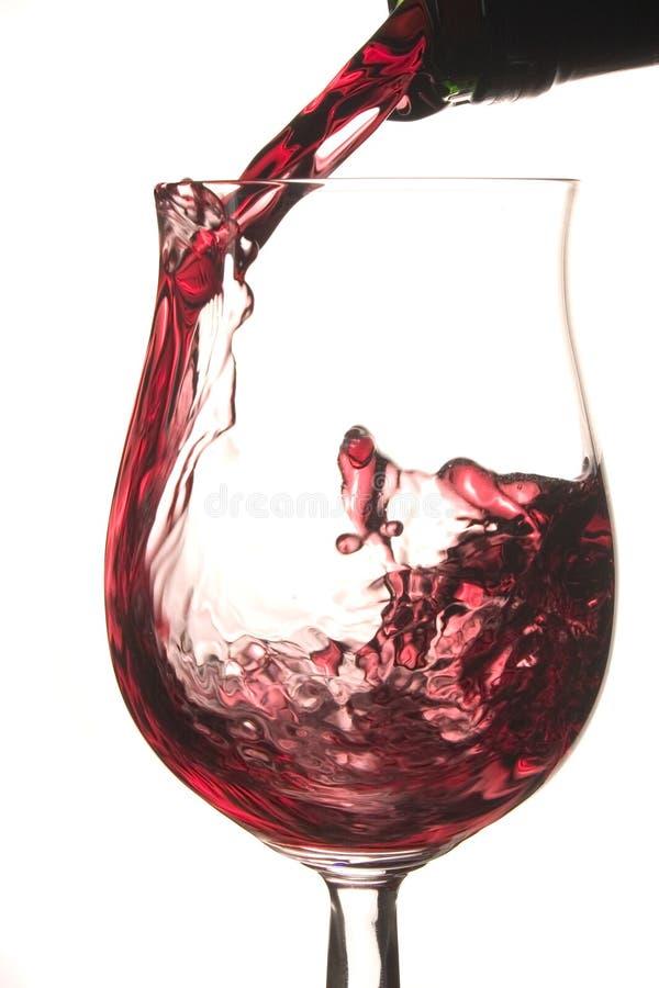 Gießen eines Glases Rotweins lizenzfreie stockfotos