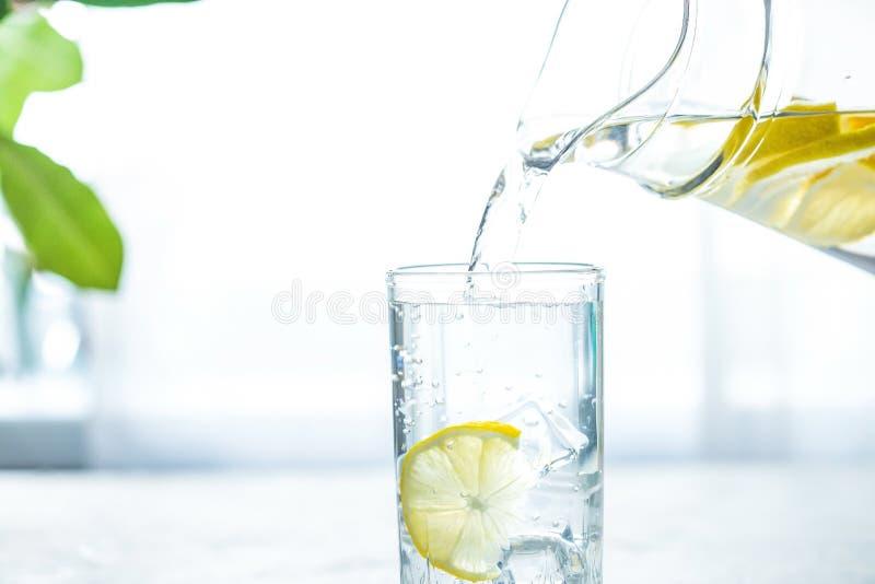Gießen eines Glases Wassers mit Zitrone, Eis und Minze auf einer weißen Tabelle stockfotografie
