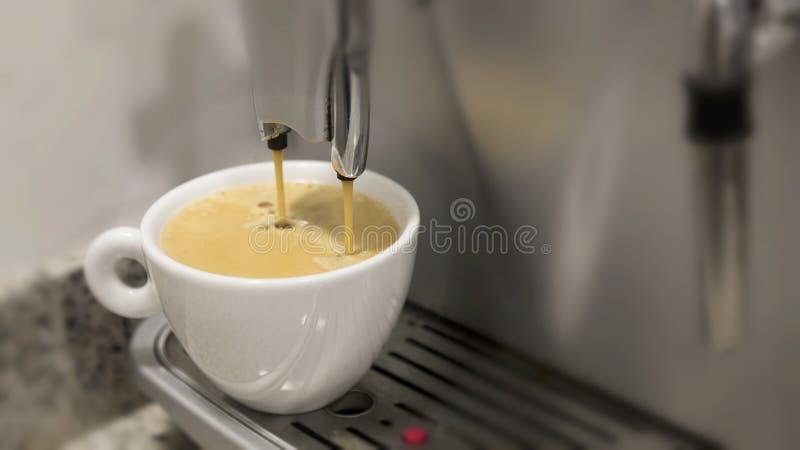 Gießen eines Kaffeeespressos auf einer Maschine in einem weißen Becher stockfotografie