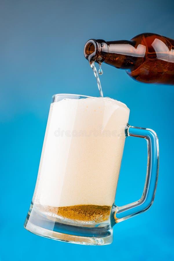 Gießen Sie das Bier in ein Glas lizenzfreies stockbild