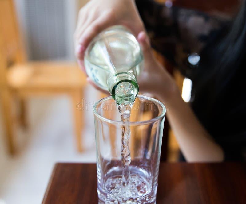 Gießen Sie ein weniges Wasser in ein Glas lizenzfreie stockfotografie