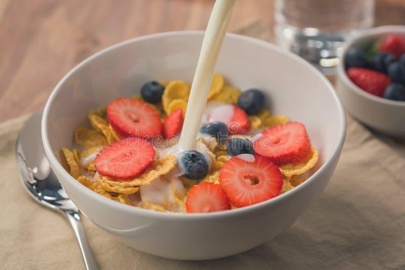 Gießen Sie Milch in Corn Flakes mit Beeren in der weißen Schüssel zum Frühstück auf Tabelle stockfotos