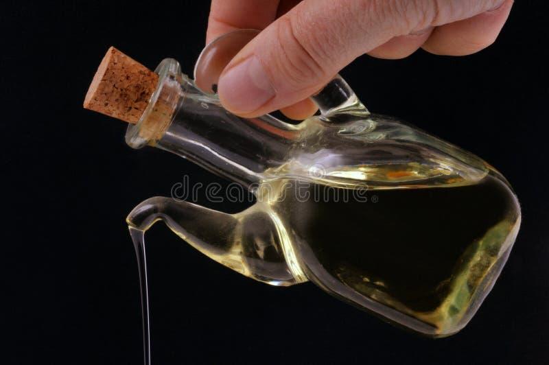 Gießen Sie Olivenöl mit einer Karaffe stockbilder
