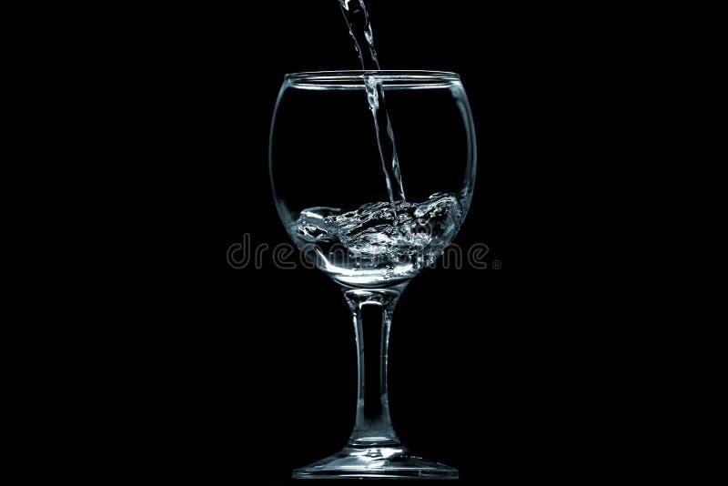 Gießen Sie Wasser in Glas auf schwarzem Hintergrund stockfotos