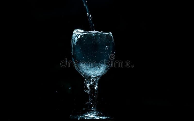 Gießen Sie Wasser in Glas auf schwarzem Hintergrund stockfoto