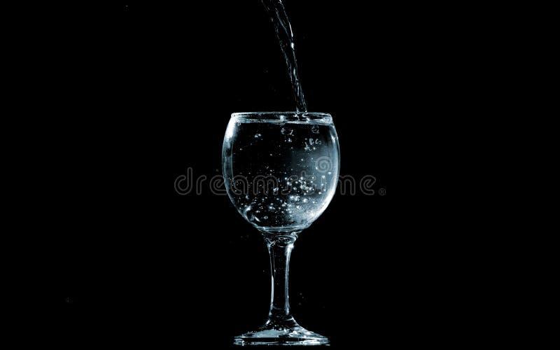 Gießen Sie Wasser in Glas auf schwarzem Hintergrund stockfotografie