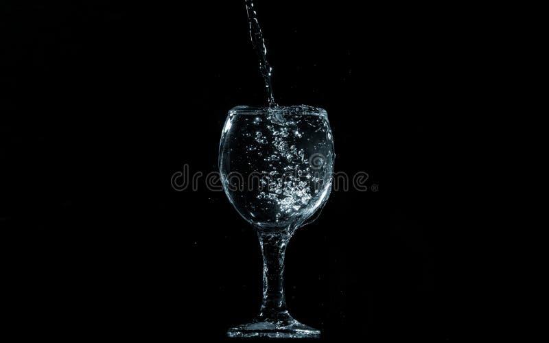 Gießen Sie Wasser in Glas auf schwarzem Hintergrund stockbilder