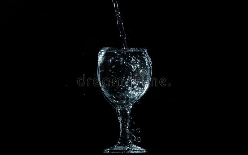 Gießen Sie Wasser in Glas auf schwarzem Hintergrund lizenzfreie stockbilder
