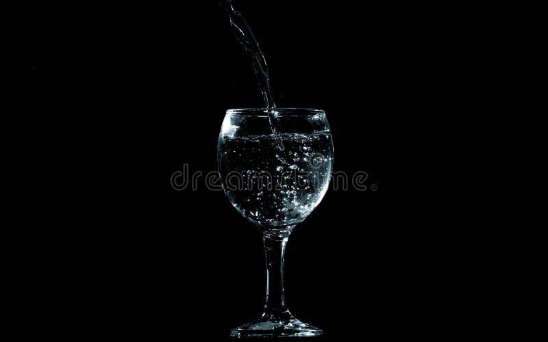 Gießen Sie Wasser in Glas auf schwarzem Hintergrund lizenzfreies stockfoto