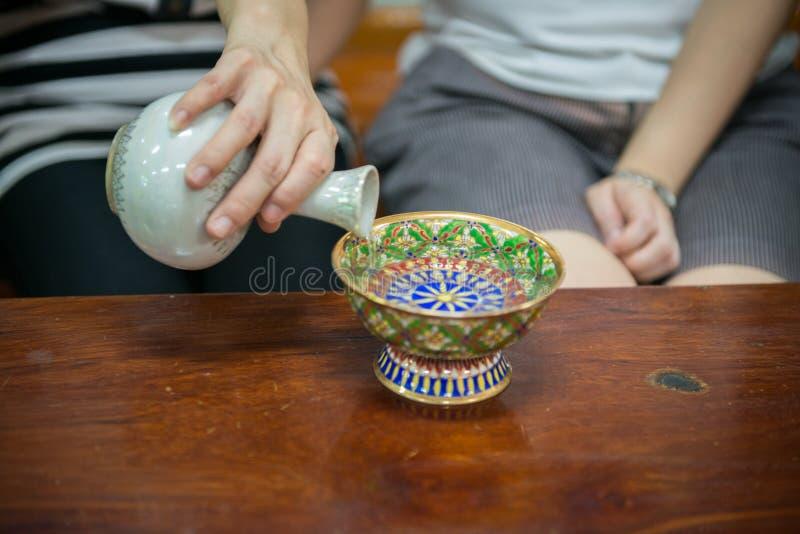 Gießen Sie zeremonielles Wasser mit Porzellan lizenzfreie stockbilder