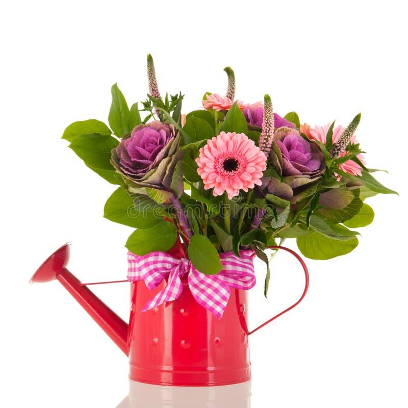 Gießkanne mit Blumenstraußblumen stockbilder