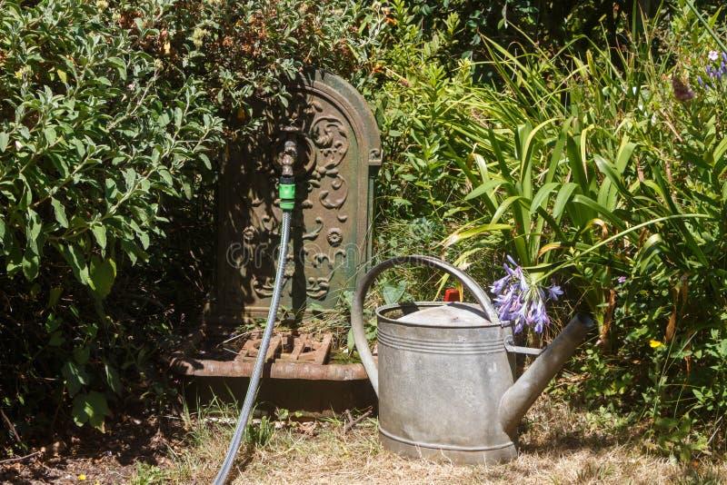 Gießkanne, Schlauch und Brunnen in einem Garten stockfoto