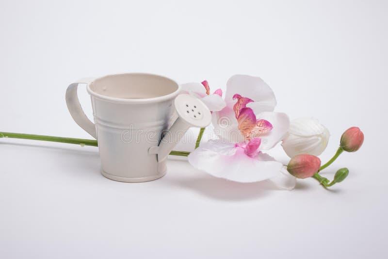 Gießkanne und ein Blumenstrauß stockfoto