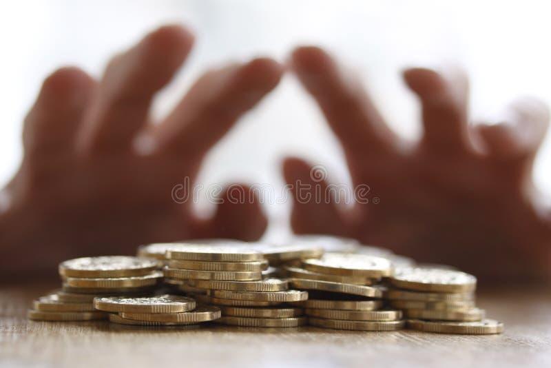 Gierige Hand, die heraus für Stapel von goldenen Münzen ergreift oder erreicht Abschluss-oben - Konzept für Steuer, Betrug und Ha lizenzfreies stockbild