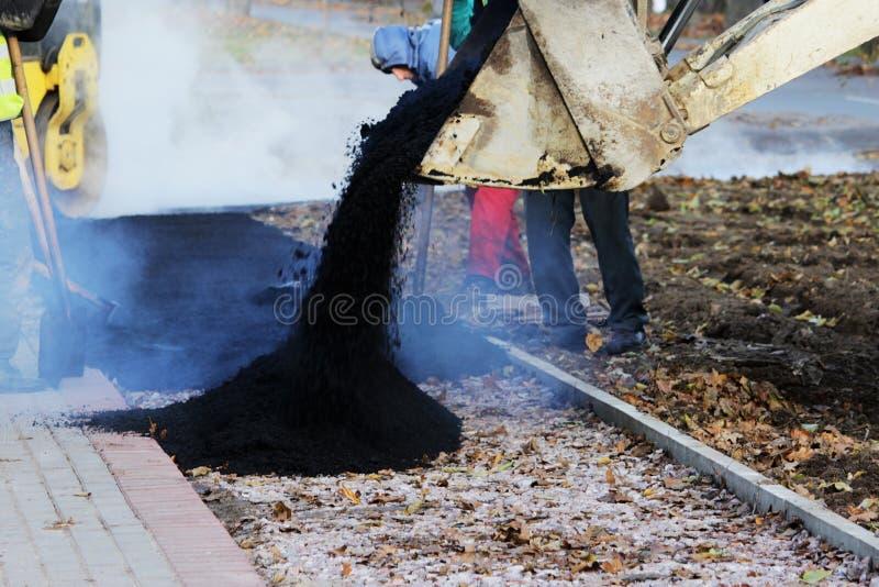 giet de tractor minilader de asfaltkruimel tijdens de reparatie van de fietsweg naast uit de stoepbestrating stock afbeelding