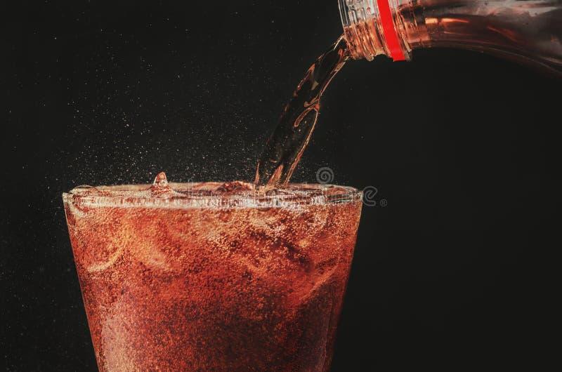 giet kola van de fles aan glas en bellensoda op zwarte rug stock foto's