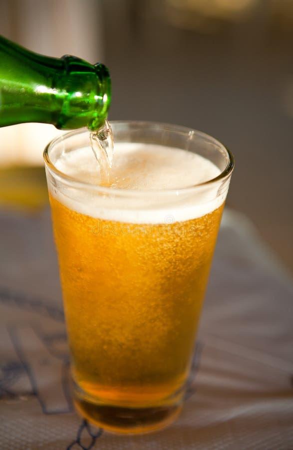 Gietend bier in glas stock foto's
