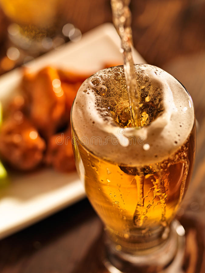 Gietend bier met kippenvleugels op achtergrond. stock fotografie