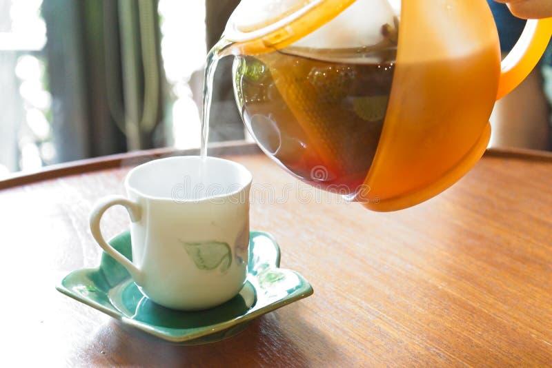 Gietend een pot van thee in een wit glas dat op schotel op rond-gevormde houten lijst plaatste stock afbeelding