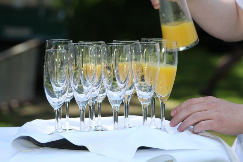 Gietend jus d'orange in champagnefluiten royalty-vrije stock foto's