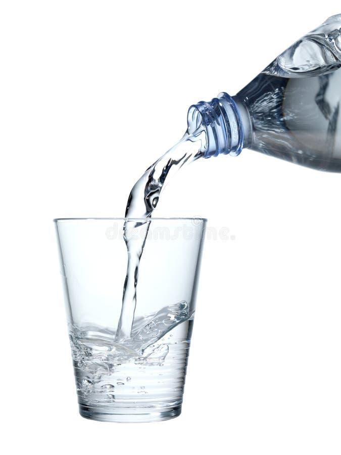 Gietend mineraalwater in een waterglas stock foto