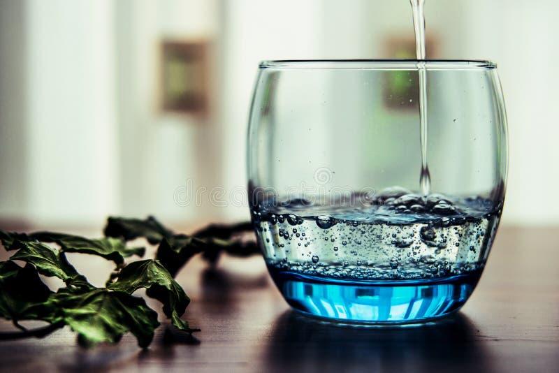Gietend Mineraalwater in het Glas stock fotografie