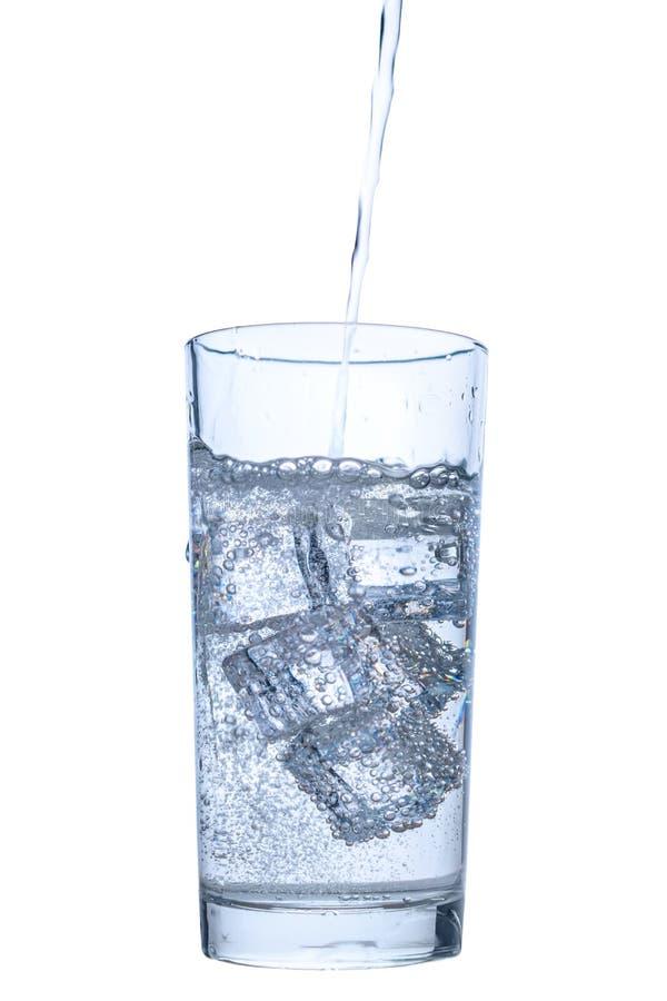 Gietend mineraalwater in transparant die glas met ijs en bellen over witte achtergrond, dichte omhooggaand worden geïsoleerd royalty-vrije stock foto