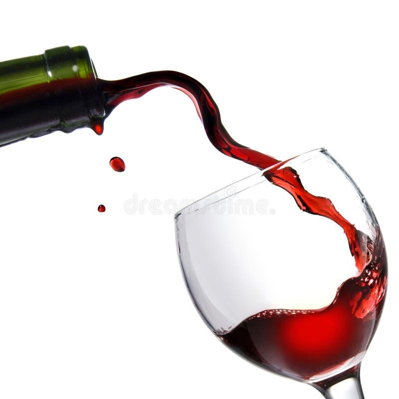 Gietend rode wijn in glasdrinkbeker die op wit wordt geïsoleerd stock afbeelding