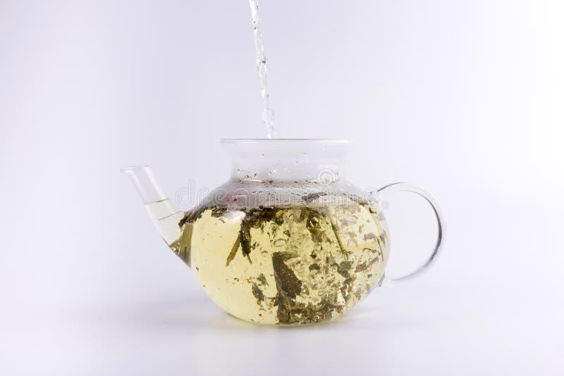 Gietend warm water aan de glastheepot met aftreksel, dat op wit wordt geïsoleerd royalty-vrije stock foto's