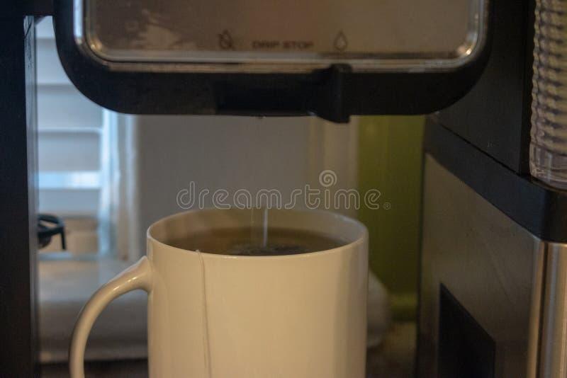 Gietend warm water in in een kop op een zwarte achtergrond royalty-vrije stock foto