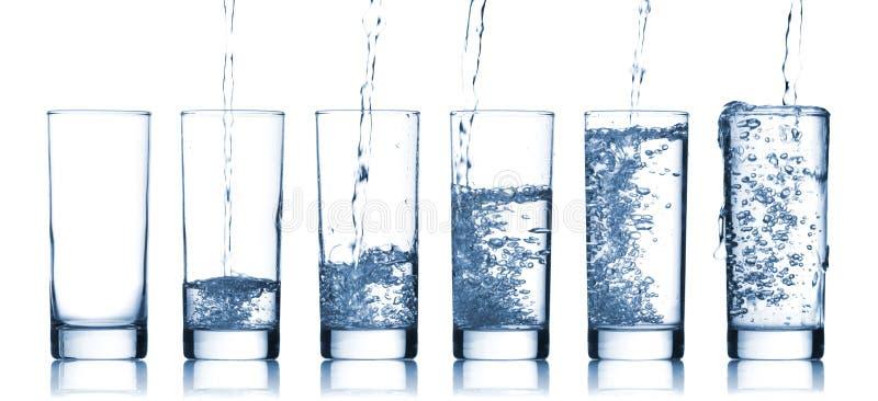 Gietend water binnen aan een glas royalty-vrije stock afbeeldingen