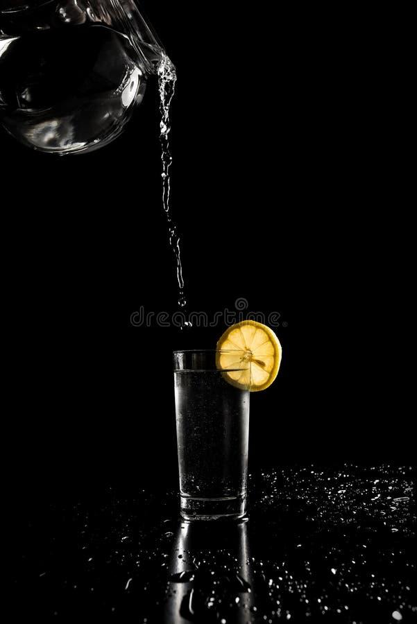 Gietend water binnen aan een lang glas stock afbeeldingen