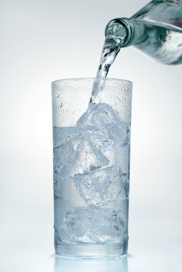 Gietend water in een glas stock afbeelding
