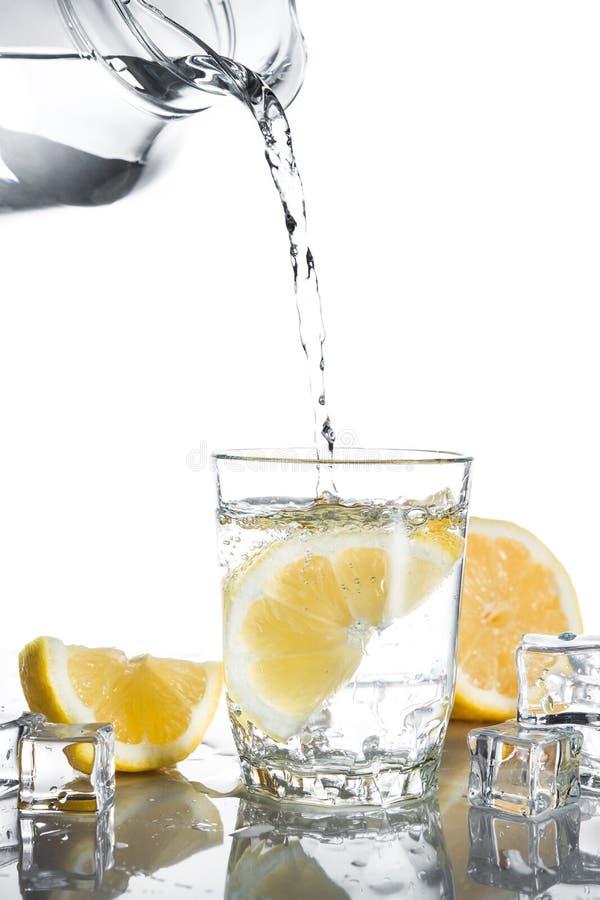 Gietend water in glas met citroenen en ijs royalty-vrije stock foto's