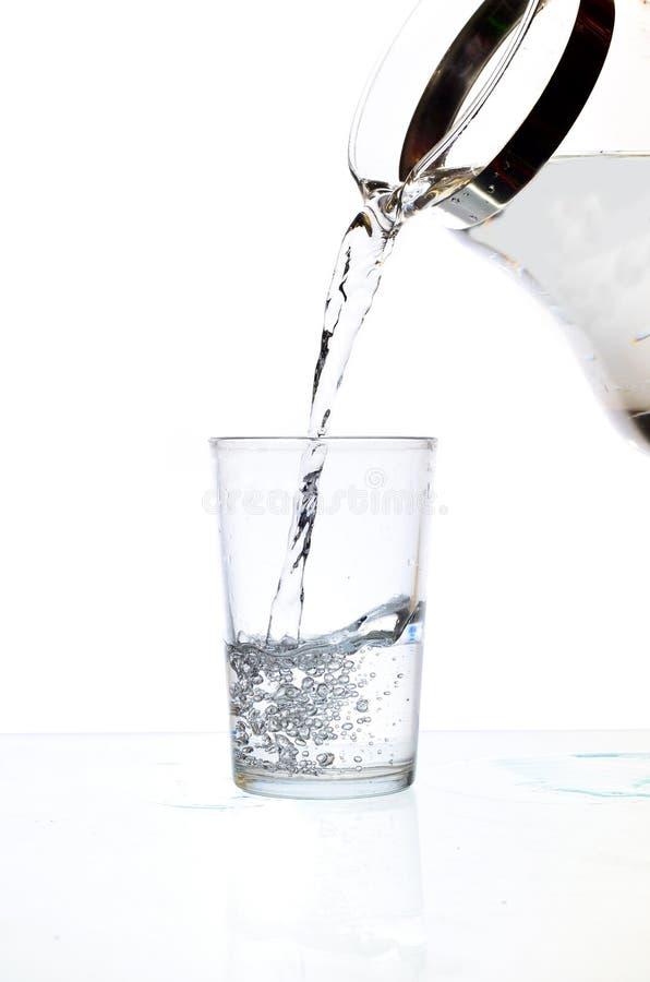 Gietend water van glaswaterkruik stock afbeeldingen