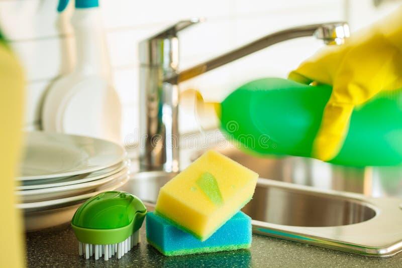 Gietende dishwashing vloeistof bij de was van de sponskeuken het schoonmaken stock foto's
