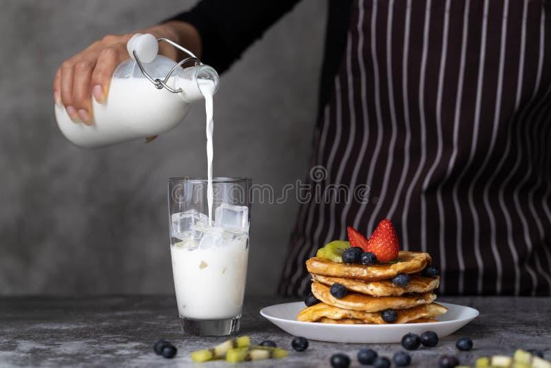 Gietende melk binnen aan glas royalty-vrije stock afbeeldingen