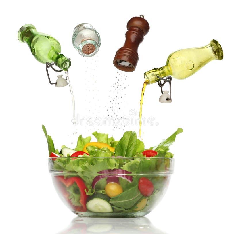 Gietende specerijen op een kleurrijke salade. stock afbeelding