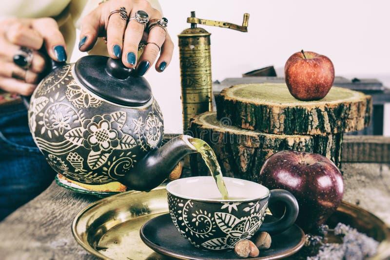 Gietende thee van theepot op oude retro houten lijst stock afbeelding